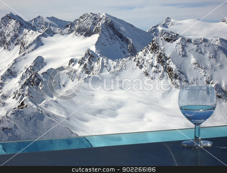 Drink in Alps stock photo, Otztal Alps viewed from the balcony of the bar on the top of Tiefenbachkogl (3309 m) in the Solden ski resort (Austria) with the glass of drink standing on the external bar surrounding the balcony. by Krzysztof Nahlik