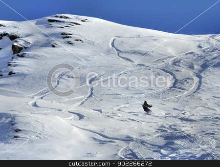 Snowboarder stock photo, Snowboarder and off-piste tracks on snow in sunset light by Krzysztof Nahlik