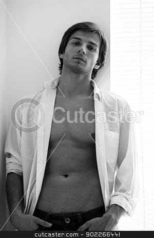 Young sexual man with naked torso stock photo, Black and white young sexual man with naked torso near the window by yekostock