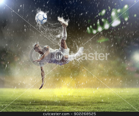 football player striking the ball stock photo, football player in white shirt striking the ball at the stadium under the rain by Sergey Nivens