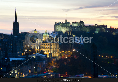 View of Edinburgh Castle at sunset stock photo, View of a floodlit Edinburgh Castle on the skyline at sunset with the lights of the city and illuminated landmarks in the foreground by Stephen Gibson