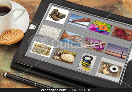 viewing pictures on digital tablet stock photo, reviewing image library (grid of thumbnails) on a digital tablet computer, table with a cup of coffee; all displayed pictures copyright by the photographer by Marek Uliasz