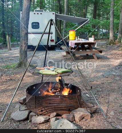 Campsite Meal stock photo, An outdoor grill at a Pennsylvania State Park with a picnic table and camping trailer in the background. by Delmas Lehman