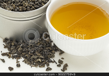 gunpowder green tea stock photo, gunpowder green tea - a white cup of drink and loose leaves on canvas by Marek Uliasz