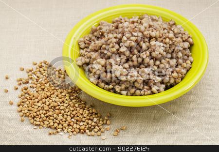 buckwheat kasha cooked stock photo, bowl of cooked buckwheat kasha with roasted grain sprayed over canvas background by Marek Uliasz