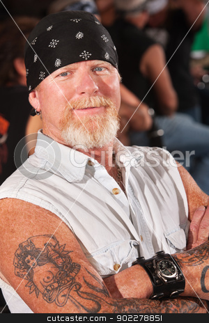 Smiling Mature Thug stock photo, Smiling middle aged motorcycle gang man with folded arms by Scott Griessel