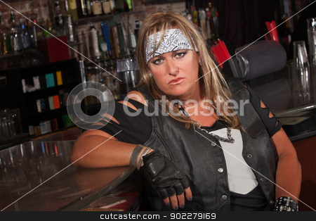 Tough Female Gang Member stock photo, Frowning female motorcycle gang member sitting in bar by Scott Griessel
