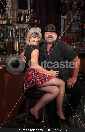 Happy Biker Gang Couple in Bar stock photo, Happy middle aged motorcycle gang couple sitting at bar counter by Scott Griessel