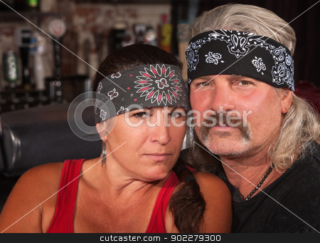 Serious Middle Aged Couple in Bar stock photo, Serious middle aged couple in bandannas at a bar by Scott Griessel
