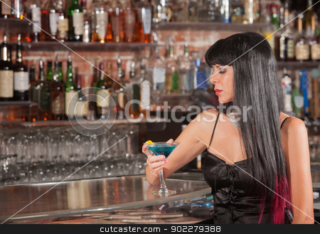 Lonely Woman Drinking in Bar stock photo, Lonely woman in black hair with martini in bar by Scott Griessel