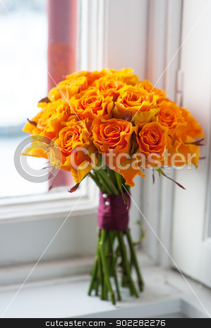 orange rose wedding bouquet stock photo, orange wedding bouquet of roses on a windowsill by a window by Lee Avison