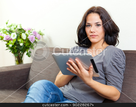 Woman using a touchpad stock photo, Young woman sit on a sofa and using an electronic tablet by tristanbm