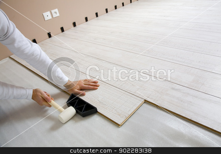 Worker laying laminated stock photo,  Worker laying a floor with laminated flooring boards  by Laurent Renault