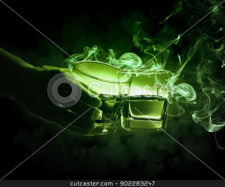 Two glasses of green absinth stock photo, Hand holding one of two glasses of green absinth with fume going out by Sergey Nivens