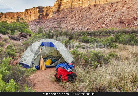 river camping in Canyonlands stock photo, sunrise over river camping in Canyonlands National Park- a tent with canoe paddle and waterproof bags on the shore of Green River by Marek Uliasz