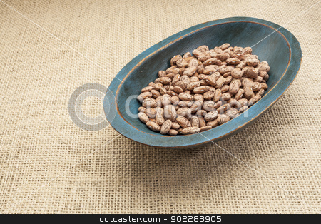 pinto bean stock photo, pinto (speckled) bean in a rustic wood bowl against burlap canvas by Marek Uliasz