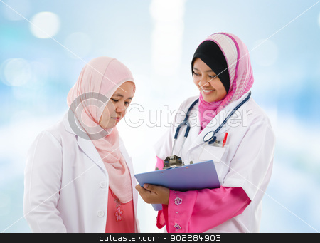 Two Southeast Asian Muslim medical doctor stock photo, Two Southeast Asian Muslim medical doctor discussing on patient medical report, standing in hospital by szefei