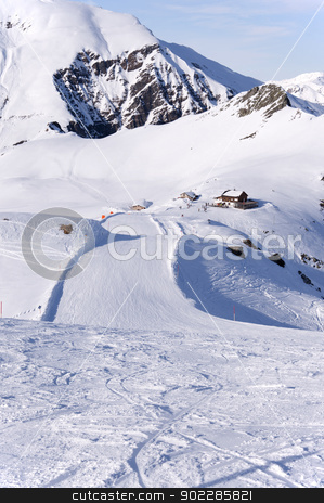 Ski run and hut in Alps stock photo, Zillertal Alps in Austria, ski piste and hut viewed from the summit of Tuxkogel mountain at sunset light by Krzysztof Nahlik