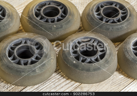 wheels for inline skating stock photo, old worn out wheels for inline skating on wooden surface by Marek Uliasz