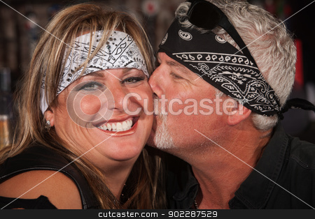 Mature Bearded Man Kisses Woman stock photo, Smiling woman in bandanna being kissed by handsome mature man by Scott Griessel