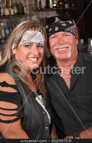 Smiling Couple in Bandannas stock photo, Handsome middle aged couple in leather and bandanna in bar by Scott Griessel