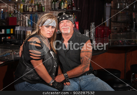 Sad Biker Woman with Grinning Man stock photo, Grinning man with tattoo holds hand of mad woman in bar by Scott Griessel