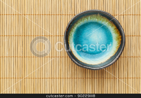 empty bowl and bamboo mat stock photo, small empty ceramic bowl (sauce dish) with blue enamel on bamboo placemat by Marek Uliasz