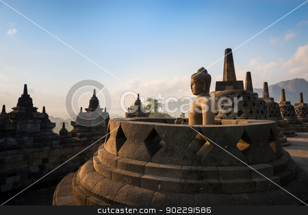Buddha in Borobudur Temple at sunrise. Indonesia.  stock photo, Buddha statue in open stupa in Borobudur, or Barabudur, temple Jogjakarta, Java, Indonesia at sunrise. It is a 9th-century Mahayana temple and the biggest  Buddhist Temple in Indonesia. by Iryna Rasko