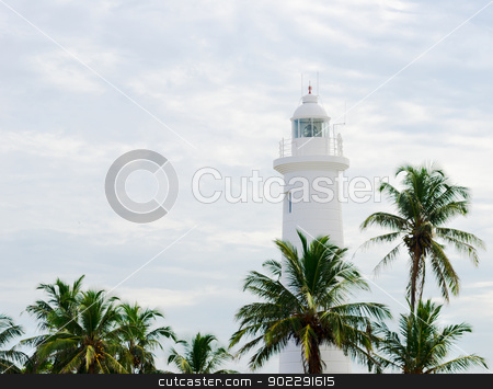 White lighthouse under tropical palms  stock photo, White lighthouse above palm tops on cloudy sky background, Galle Sri Lanka by Iryna Rasko