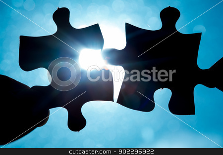 Hand holding two jigsaw pieces stock photo, Hand holding two jigsaw pieces up to the sunlight by Wavebreak Media