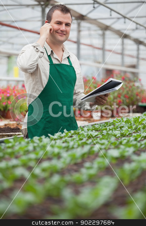 Smiling man on the phone and taking notes in greenhouse stock photo, Smiling man on the phone and taking notes in greenhouse in garden center by Wavebreak Media