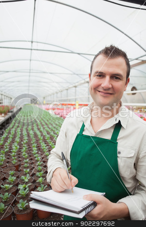 Smiling man taking notes in greenhouse stock photo, Smiling man taking notes in greenhouse nursery by Wavebreak Media