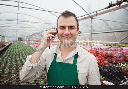 Employee on the phone in greenhouse stock photo, Smiling employee on the phone in greenhouse in garden center by Wavebreak Media