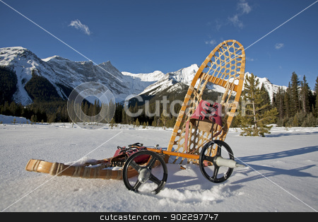 snowshoe gear in the snow stock photo, vintage snowshoe gear in the snow with mountains in the background by Barna Tanko