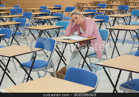 Student sitting at desk thinking  stock photo, Student sitting at desk while thinking  by Wavebreak Media