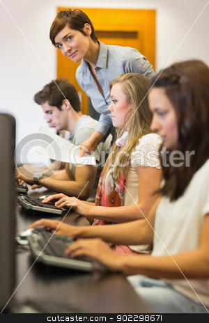 Students sitting at the computer with teacher looking on stock photo, Students sitting at the computer while teacher is looking on in college computer class by Wavebreak Media