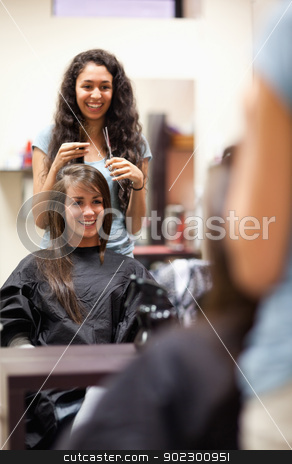 Portrait of a woman making a haircut stock photo, Portrait of a woman making a haircut standing up by Wavebreak Media