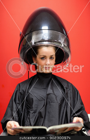 Portrait of a young woman under a hairdressing machine stock photo, Portrait of a young woman under a hairdressing machine while looking at the camera by Wavebreak Media