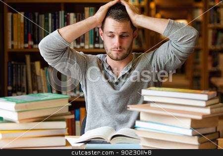Tired student having too much to do stock photo, Tired student having too much to do in a library by Wavebreak Media