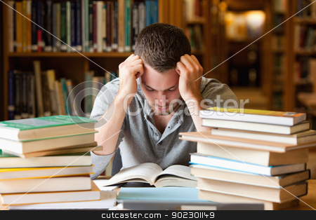 Tired student having a lot to read stock photo, Tired student having a lot to read in a library by Wavebreak Media