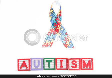 Autism awareness ribbon above letter blocks spelling autism stock photo, Autism awareness ribbon above letter blocks spelling autism on white background by Wavebreak Media