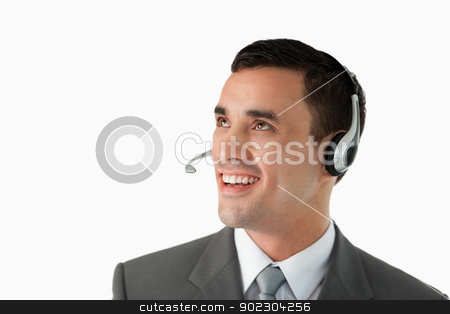 Close up of young male professional with headset on stock photo, Close up of young male professional with headset on against a white background by Wavebreak Media