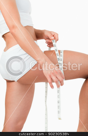 Portrait of a woman measuring her thigh stock photo, Portrait of a woman measuring her thigh against a white background by Wavebreak Media