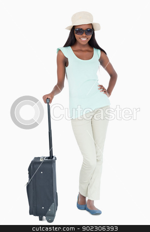 Smiling young woman with her suitcase stock photo, Smiling young woman with her suitcase against a white background by Wavebreak Media