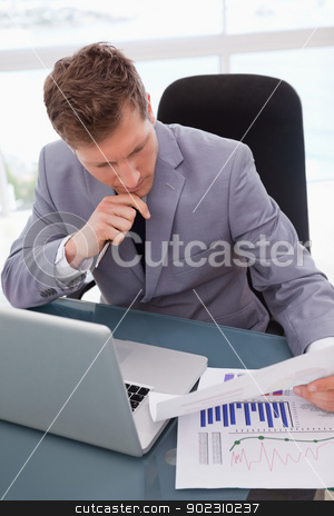 Businessman looking at market research results stock photo, Businessman at his desk looking at market research results by Wavebreak Media