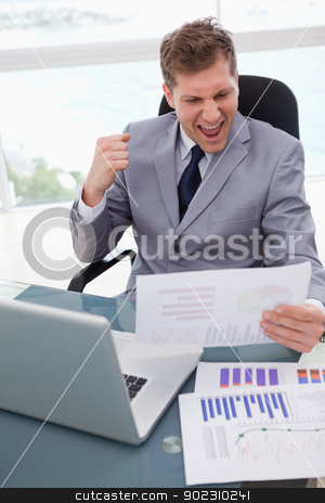 Businessman loves the result of market research stock photo, Businessman at his desk loves the result of market research by Wavebreak Media