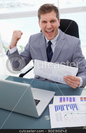 Businessman celebrating market research results stock photo, Businessman at his desk celebrating market research results by Wavebreak Media