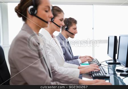 Side view of customer service assistants stock photo, Side view of customer service assistants at work by Wavebreak Media