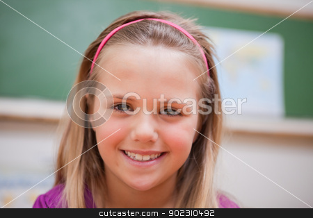 Close up of a schoolgirl posing stock photo, Close up of a schoolgirl posing in a classroom by Wavebreak Media