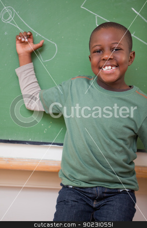 Portrait of a schoolboy showing something stock photo, Portrait of a schoolboy showing something on a blackboard by Wavebreak Media